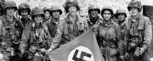 American paratrooper, among the first to make successful landings on the continent, holds a Nazi flag captured in a village assault. Utah Beach, St. Marcouf, France. 8 June 1944